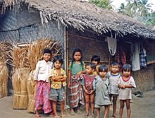 Group of smiling children in front of a thatch-roofed house