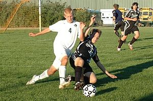 Sliding tackle - Sliding tackle performed by the player in black.