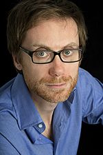 A blue-eyed, ginger-bearded man in a blue shirt and glasses looking into the camera before a black background.