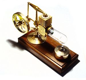 Applications of the Stirling engine - A desktop alpha Stirling engine. The working fluid in this engine is air. The hot heat exchange is the glass cylinder on the right, and the cold heat exchanger is the finned cylinder on the top. This engine uses a small alcohol burner (bottom right) as a heat source