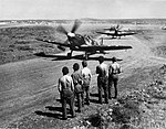 Supermarine Spitfire Mark IXs of No. 73 Squadron RAF, each loaded with two 250-lb GP bombs, taxy to the runway at Prkos, Yugoslavia, for a sortie against retreating German troops and supply lines.jpg