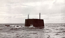 Port side view of the sail and forward deck of the nuclear submarine Triton breaking the surface of the ocean near Cadiz, Spain, with hull number 586 visible on its sail.