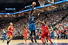 Center Sylvia Fowles scoring a basket, wearing blue, Mystics players in red, fans packed into surrounding seats