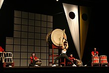 Members of Brazilian group Seiryu Daiko performing on stage with a variety of taiko.