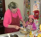 Une grand-mère portant un tablier bordeaux sur une blouse rose, racle au-dessus du plat en inox de pâte qu'elle vient de confectionner l'un des fouets de son mixeur-batteur tandis qu'à côté d'elle sa petite-fille habillée de rose fuchsia et portant un tablier identique mais rose pâle, se lèche le doigt utilisé pour gouter la pâte prélevée sur le second fouet.