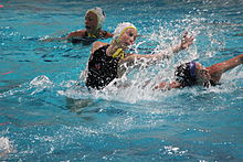 woman in water lunging for the ball