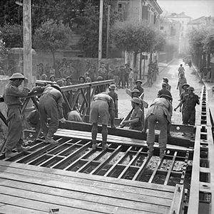 Bailey bridge - Royal Engineers construct a Bailey bridge in Italy, September 1943. Wood planks are being laid over the stringers to construct the roadbed