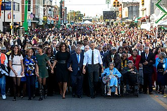 Amelia Boynton Robinson - Amelia Boynton Robinson at the start of the procession across the Edmund Pettus Bridge on March 7, 2015, the 50th anniversary of Bloody Sunday. Robinson, wearing blue, is holding President Barack Obama's left hand; John Lewis is holding Obama's right.
