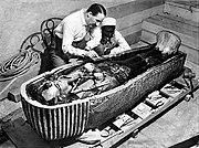 Говард Картер исследует саркофаг фараона Тутанхамона. Гробница KV62 близ Луксора, 1923 г.