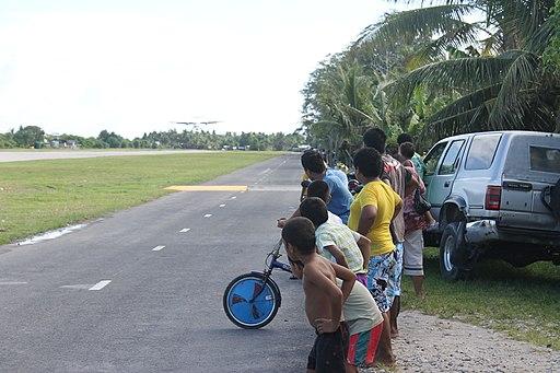 Tuvaluan kids watching plane land at Funafuti International Airport