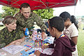 U.S. Navy Capt. Wallace Lovely, second from left, the mission commander of Pacific Partnership 2013, and Canadian Army Sgt. Corrine Burghardt, left, teach Tongan children about dental health at a Pacific 130613-N-SK590-313.jpg