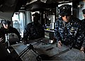 U.S. Navy Lt. Cmdr. Allison Martin, right, a navigator aboard the amphibious assault ship USS Makin Island (LHD 8), conducts detail plotting with a navigation team during sea and anchor detail as the Makin 131212-N-GT710-073.jpg