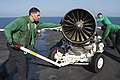 U.S. Navy Petty Officer 3rd Class Enoc Silva uses the tow bar to steer the cart as they move an F-A-18E Super Hornet engine on the flight deck of the aircraft carrier USS Harry S. Truman (CVN 75) while the ship 131020-N-ZG705-144.jpg
