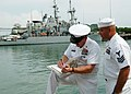 US Navy 050805-N-0962S-188 Master Chief Petty Officer of the Navy Terry Scott signs a charge-book for a chief petty officer selectee assigned to USS Devastator (MCM 6).jpg