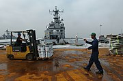 US Navy 051020-N-9866B-008 Boatswain's Mate 2nd Class Eric Hagan, right, directs a contractor on a forklift during the resurfacing of the flight deck