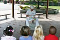 "US Navy 060831-N-7163S-003 Amphibious transport dock ship USS Cleveland (LPD 7) ""Blue Jacket Sailor"" of the Year, Culinary Specialist Seaman Sean Unterdorfer reads Yankee Doodle Dandy to the kindergarten class from.jpg"