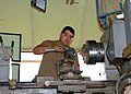 US Navy 070426-N-3560G-007 Machinery Repairman 3rd Class Christian Duarda of Naval Mobile Construction Battalion (NMCB) 4 adjust the cutting angle on a portable lathe.jpg