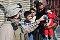 US Navy 070809-M-6412C-024 Lt. j. g. Jerry L. McNew attached to Regimental Combat Team (RCT) 6, Information Operations, hands a stuffed animal to an Iraqi boy during Operation Alljah.jpg