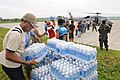 US Navy 080625-N-5961C-002 Residents of Iloilo help U.S. service members unload bottled water and rice from a helicopter assigned to the.jpg