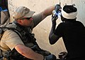 US Navy 100202-N-4971L-132 Sailor provides first aid to Haitian woman.jpg