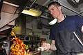 US Navy 100610-N-9327W-084 Culinary Specialist 3rd Class Nicholas Roby, from Louisville, Ky., tosses sautéed vegetables in the commanding officer's galley aboard the amphibious assault ship USS Nassau (LHA 4).jpg