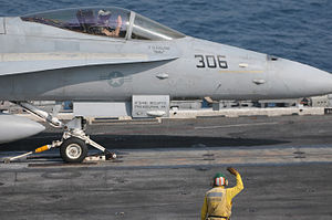 US Navy 120111-N-GZ832-227 Lt. Cmdr. Brian Tkach salutes a shooter as he prepares to launch from the flight deck of Nimitz-class aircraft carrier U.jpg