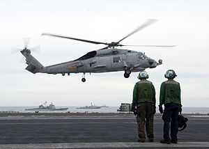 US Navy 120123-N-JL826-019 Sailors from the aircraft carrier USS Enterprise (CVN 65) stand by as an SH-60B Sea Hawk helicopter takes off during a n.jpg