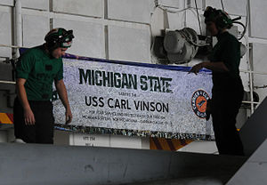 US Navy 120210-N-GZ832-035 Sailors perform maintenance on an F-A 18C Hornet in front of a signed Michigan State banner commemorating the inaugural.jpg