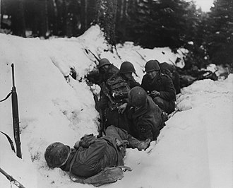 Battle of Heartbreak Crossroads - Infantrymen of the 9th Regiment, 2nd Infantry Division crouch in a snow-filled ditch, taking shelter from a German artillery barrage in the Krinkelter woods on 14 December.