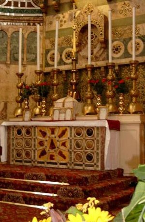 Tridentine Mass - A pre-1969 Roman Rite high altar decorated with reredos and fixed on a three step platform, below which the Prayers at the Foot of the Altar are said. Leaning against the tabernacle and two of the candlesticks are altar cards to remind the celebrant of the words when he is away from the missal