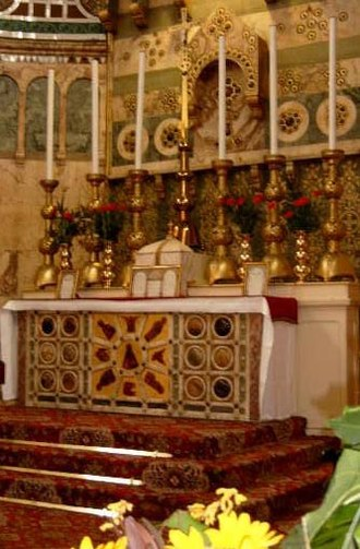 Tridentine Mass - A pre-1969 Roman Rite high altar decorated with reredos and fixed on a three-step platform, below which the Prayers at the Foot of the Altar are said. Leaning against the tabernacle and two of the candlesticks are altar cards, to remind the celebrant of the words when he is away from the missal