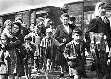 Women and children walking away from boxcars