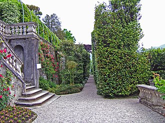 Terrace garden - Transverse view along a narrow terrace, Villa Carlotta on Lake Como, Tremezzo, Italy: stairs from an upper level are inset into the retaining wall.