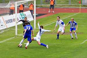 2010 Latvian Higher League - Aleksejs Soleičuks tries to block a shot by Vitalijus Kavaliauskas on a goal guarded by Jevgēņijs Sazanovs in the match between SK Liepājas Metalurgs and FC Tranzit