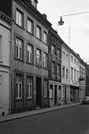 foto van Bakstenen huis met zijtrapgevel en in de voorgevel een ingang en vensters in naamse steen
