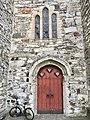 Voss Church (Voss kirke-kyrkje, Vangskyrkja) 13th-c stone church, Voss, Norway 2016-10-25 -05- front door portal, stone wall, stained glass window.jpg