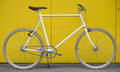 White single-speed bicycle on yellow background.png