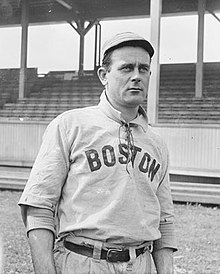 "A man in a white cap and baseball jersey with a high collar and ""Boston"" written across the chest stands in front of a grandstand."