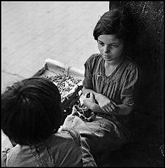 """Children In Naples, Italy"". Little girl selling beans. Photographed by Lieutenant Wayne Miller, July 1944. U.S. Navy Photograph, now in the collections of the National Archives.jpg"