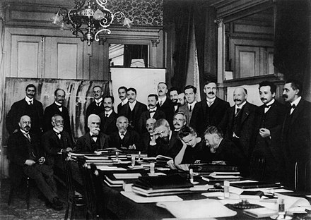 At First Solvay Conference (1911), Curie (seated, second from right) confers with Henri Poincare; standing, fourth from right, is Rutherford; second from right, Einstein; far right, Paul Langevin 1911 Solvay conference.jpg