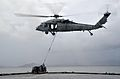 A U.S. Navy MH-60S Seahawk helicopter assigned to Helicopter Sea Combat Squadron (HSC) 25 transports a pallet of water from the dry cargo and ammunition ship USNS Charles Drew (T-AKE 10) in the Philippine Sea to 131114-N-ZT599-028.jpg