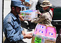 Afghan National Civil Order Police and Coalition Forces load boxes of school supplies onto a truck to distribute them to a nearby school. (4678253932).jpg