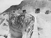 A road at the edge of a cliff with trucks driving both ways along it.