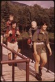BACKPACKING FAMILY WITH CHILDREN ON THEIR BACKS CROSSES THE BRIDGE AT MARCY DAM, NEW YORK, IN THE ADIRONDACK FOREST... - NARA - 554506.tif