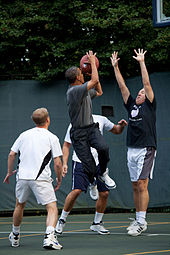 Obama about to take the shot while three other players look at him. One of those players is holding is arms up in an attempt to block Obama.