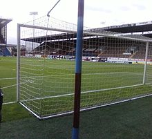 In the foreground is a football net. Through the net, a football stand with wooden seats can be seen in addition to part of a grass football pitch. In the top left corner there is a floodlight pylon.