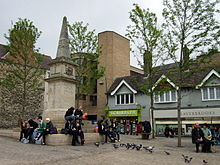 A paved square with a war memorial. People sitting on the steps. Pigeons waiting to be fed. Shops in the background.