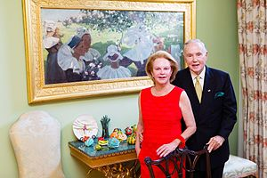 Brian P. Burns - Brian P. Burns and his wife Eileen photographed in front of a painting by Walter Chetwood-Aiken from his collection of Irish art.