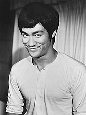 photo en noir et blanc d'un asiatique (Bruce Lee) souriant