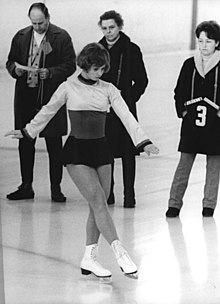 Black and white photo of a young woman, dressed in a short dress and white ice skates, executing figures on ice, while three people, two men and one woman, look on behind her